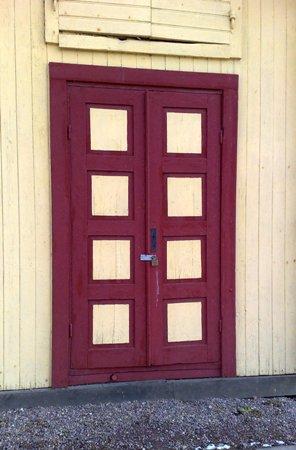 Rödrutig dörr med hänglås på gult hus