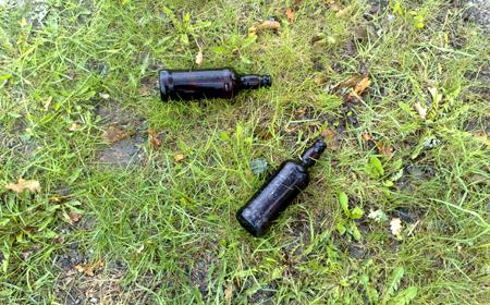 två tomflaskor i gräset