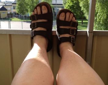Toffelfötter på balkongräcket