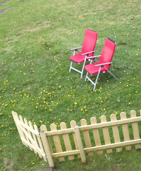 två röda stolar på gräset