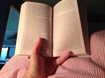Läser en bok i sängen