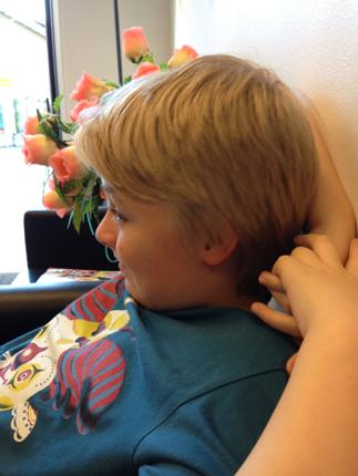 En långhårig pojke hos frisören.