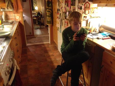 Elias med mobilen i mitt kök