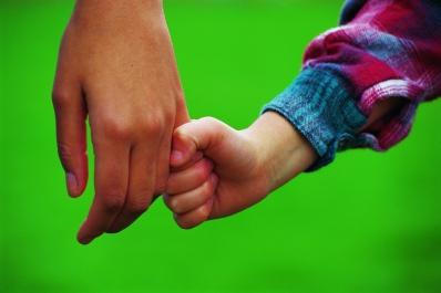Barnhand håller vuxenhand