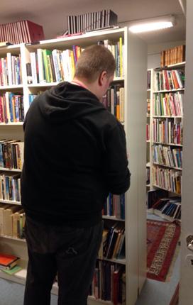 Johan plockar i bokhyllorna på Myrorna