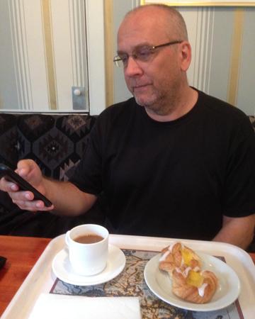 Pe med mobil och wienerbröd