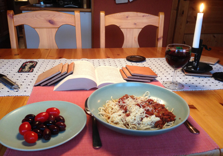 Pasta med tomater oliver vin bok o tänt ljus