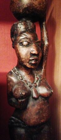 Afrikansk kvinna håller i bröstet