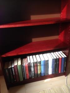 Nedersta hyllplanet är olästa böcker från vännen A.