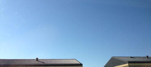 Blå himmel över hustaken