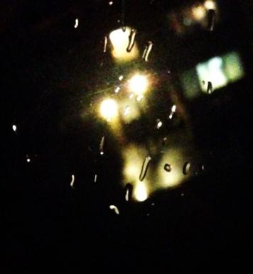 Regn på fönster och lampor utanför i mörkret