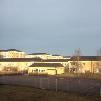 Gula hus och grå himmel vid tennisbanan