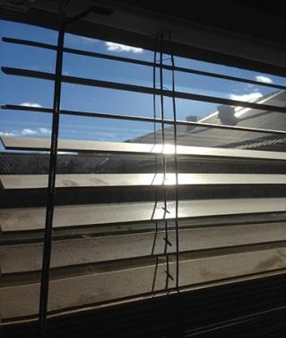 Solen genom skitiga persienner