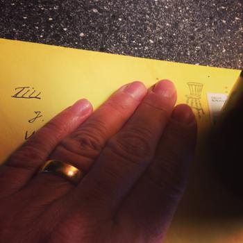Gult kuvert med hand